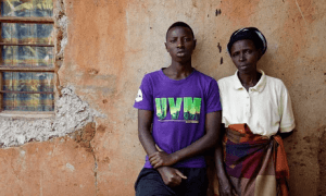 Olivier Utabazi, 19, and his mother, Epiphane Mukamakombe, 44, outside their home in Kibilizi. The son of rape, he is her only close surviving relative, after her family were killed in the genocide. Photograph: Stephen Hird / Channel 4 News. (The Guardian)
