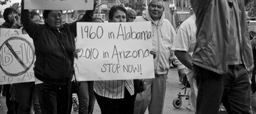 photo of rally with protestor holding sign that reads 1960 in Alabama 2010 in Arizona