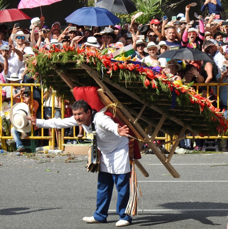 man carrying a monumental silleta in the Medellin Feria de las Flores
