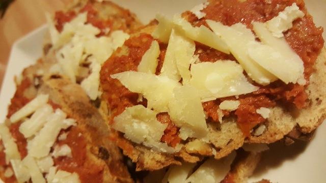 Bocada de parmesan sus son lièit de tomatas secadas / Tapas de parmesan sur lit de tomates séchés
