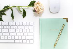 A mint green notebook and gold pen sit next to a white rose and Apple keyboard