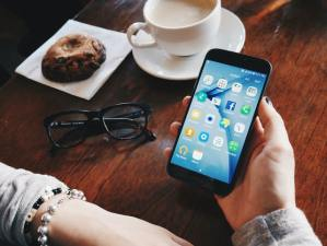 Hands rest upon on a cafe table while holding a cell phone open to social media icons and apps