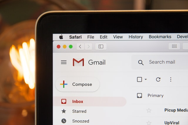 The corner of a computer shows the Gmail logo.