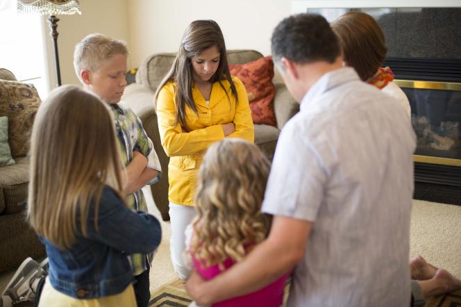 family praying in a circle