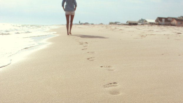 a woman walks on the beach, leaving footsteps in the sand