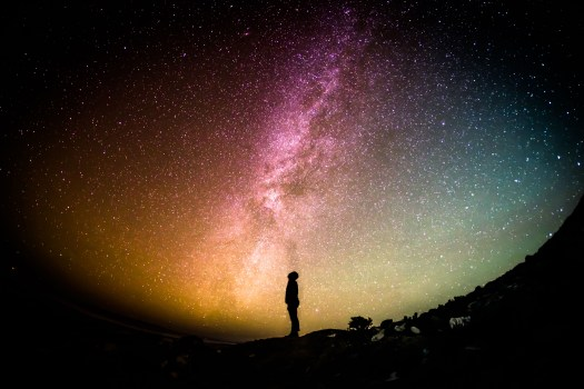 star-filled colorful night sky with a person silhouette