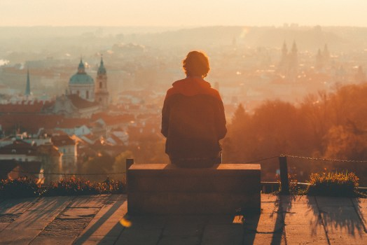person looking at a view of old city and sunset