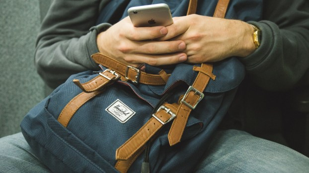 man sitting with a backpack on lap using cell phone