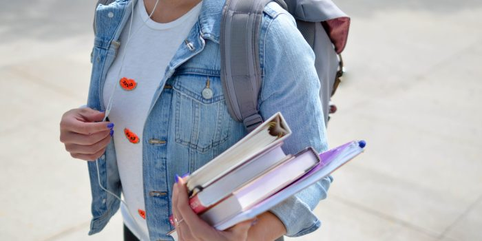 Person with backpack and books