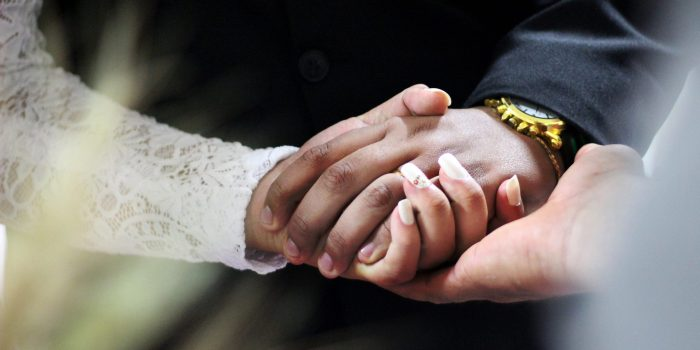People at a wedding holding hands