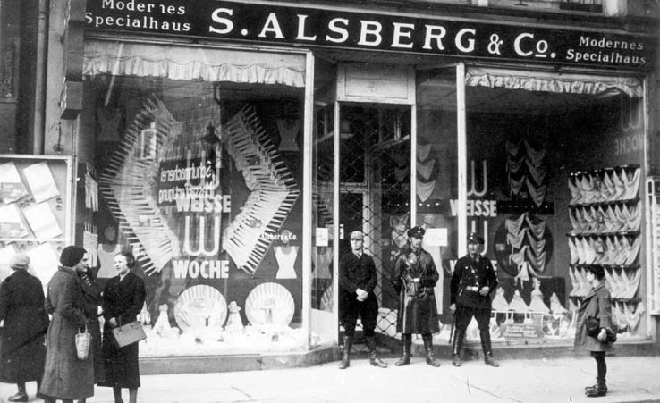 Das jüdische Kaufhaus Alsberg wird von Nazis blockiert. Man sieht, wie die Wachposten ihre Macht genießen.