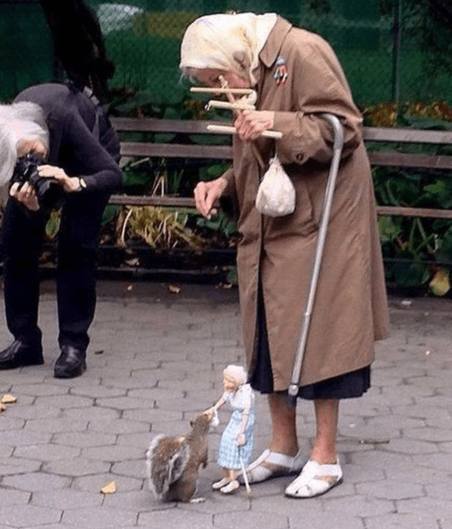 Old woman uses a marionette of herself to feed squirrels in the park