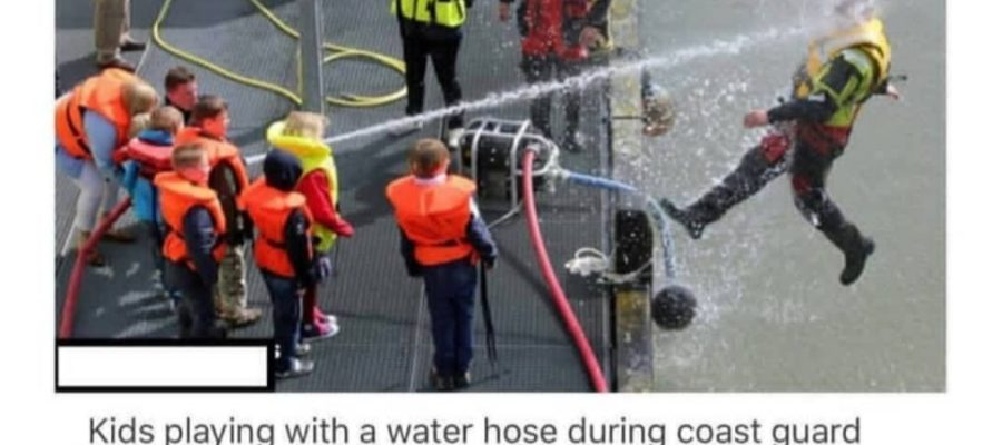 Kids play with a water hose during coast guard demonstration