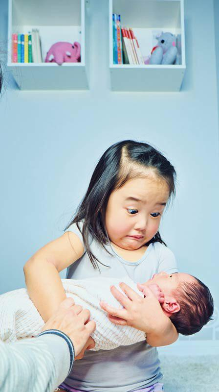 Holding baby sibling for the first time