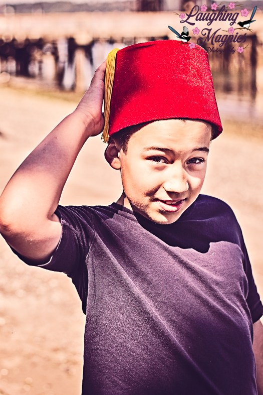 Heather Tristan of Laughing Magpies Photography in Bothell and Mill Creek, Washington, captures a young boy proudly displaying his fez, a tribute to the legacy of Matt Smith's portrayal of The Doctor on Doctor Who. The boy brought his fez along for a family photo shoot at the Mukilteo shoreline.