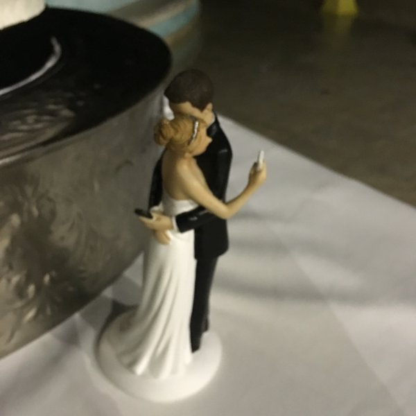 Wedding Cake Topper Featuring A Bride And Groom Checking