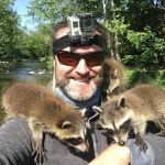 A Trio of Orphaned Baby Raccoons Adopt a Visiting Bearded Fisherman as Their Mother