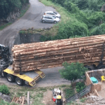 A Logging Truck Makes a Tight Turn Impressively Crossing a Small Bridge While Pulling a Full Load