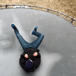 Slow Motion Video of a Teenager Jumping Onto an Ice-Covered Trampoline Shattering the Surface
