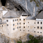 A 13th Century Slovenian Castle That Sits on a Rocky Cliffside Is Anchored Into Place by Ancient Caves
