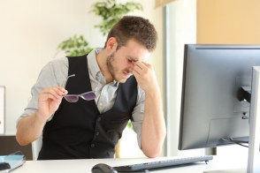 Businessman suffering eyestrain at office