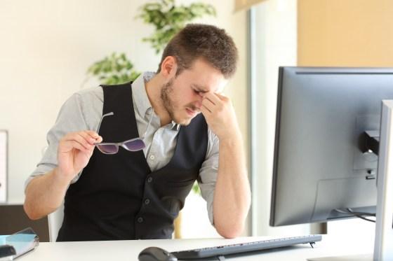 Businessman suffering eyestrain at office