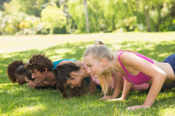 Side view of a group of fitness people doing push ups in the par