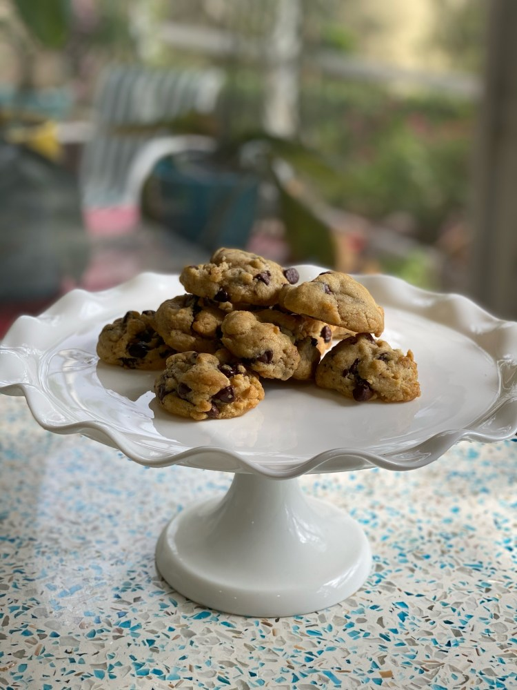 a picture of delicious-looking, golden brown, puffy chocolate chip cookies resting on a white tray.
