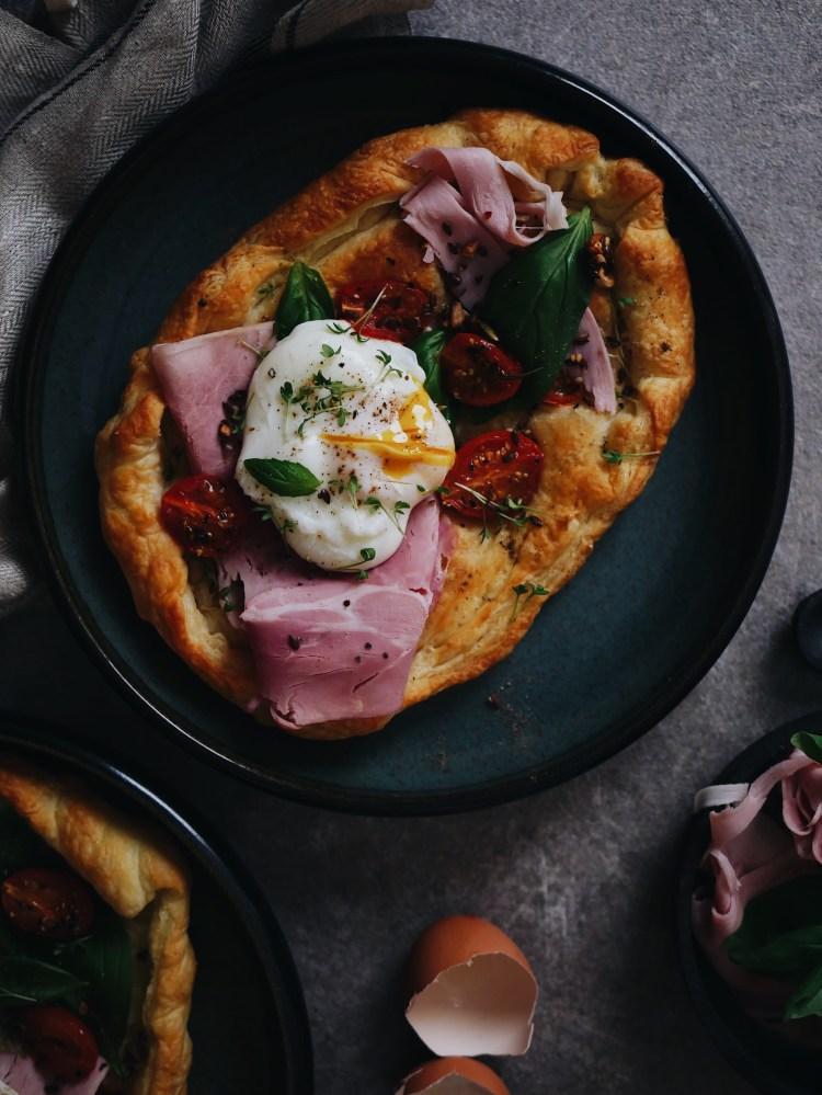 Fruehstueckspizza mit pochiertem Ei, Prosciutto und Tomaten