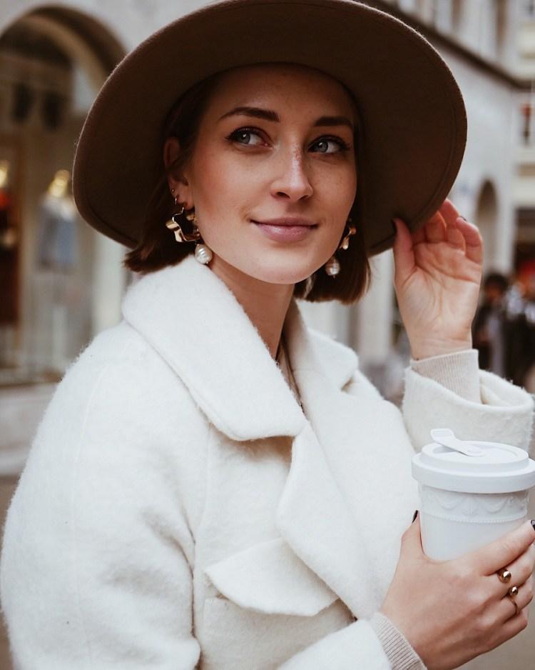 Laura Herz Weißer Mantel, Faltenrock und Cowboystiefel