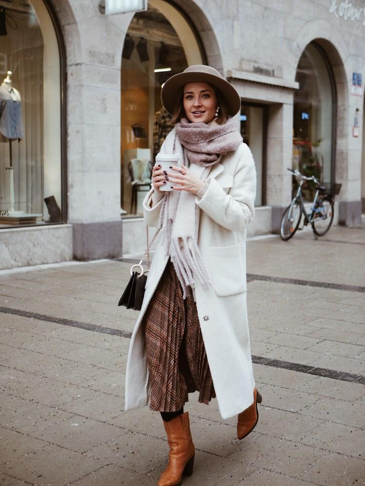 Weißer Mantel, Faltenrock und Cowboystiefel