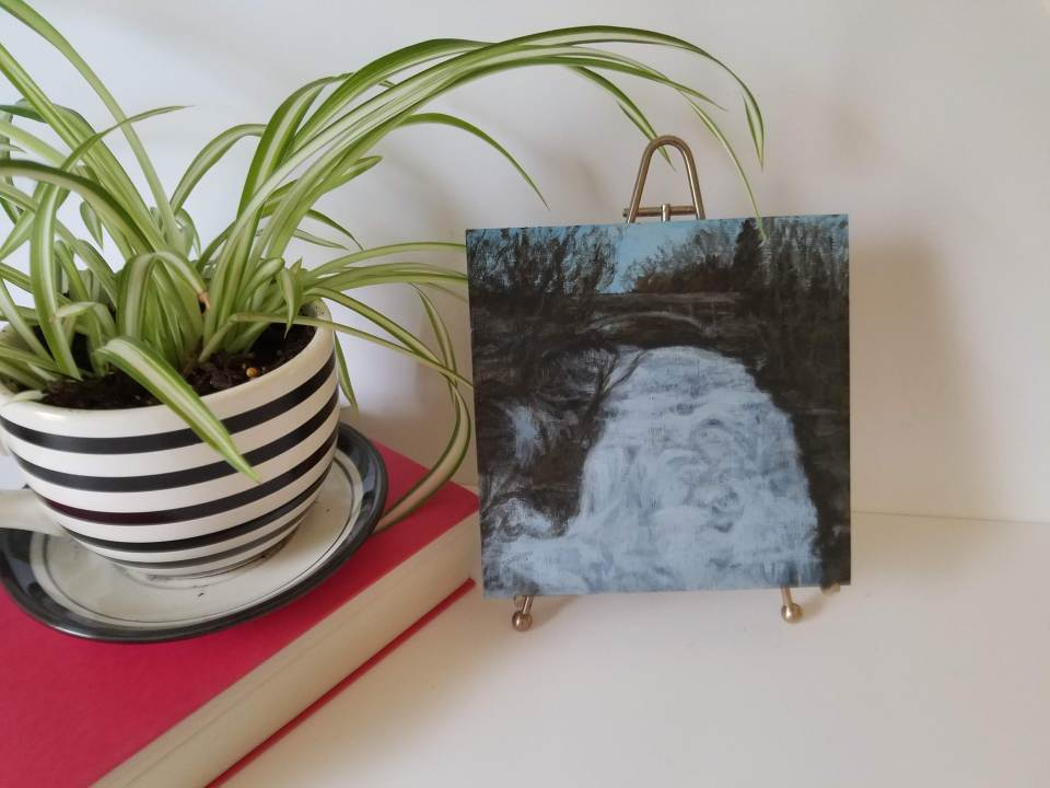 Shequaga Falls by Laura Jaen Smith. Acrylic landscape painting of frozen over waterfall Montour Falls on easel next to red book and plant.. 50 NY Waterfalls Project.
