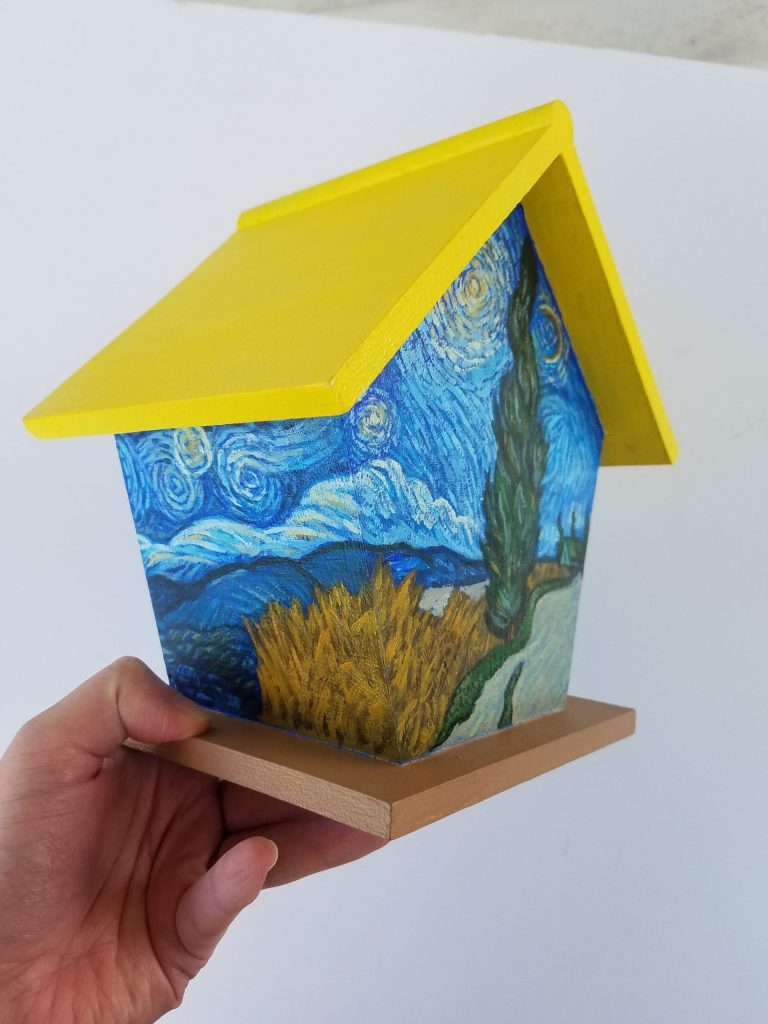 Van Gogh Birdhouse. Squared birdhouse with yellow roof, tan base. Hand-painted scene inspired by Road with Cypress and Star