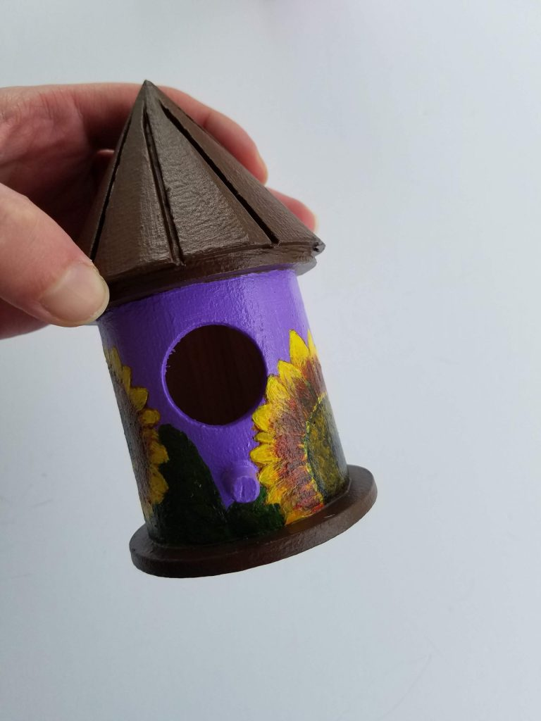 Purple Sunflower Birdhouse by Laura Jaen Smith. Small round birdhouse in hand with brown roof and base, hand-painted sunflowers with light purple background.