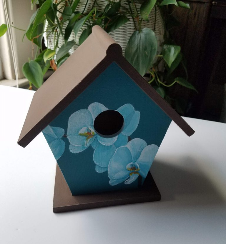 Teal Orchid birdhouse by Laura Jaen Smith. Wooden birdhouse painted white orchids around the exterior with teal blue background.