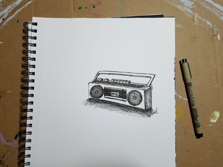 Sketchbook view with pen of Radio by Laura Jaen Smith. Black and white ink drawing of 90's style boom box cassette player