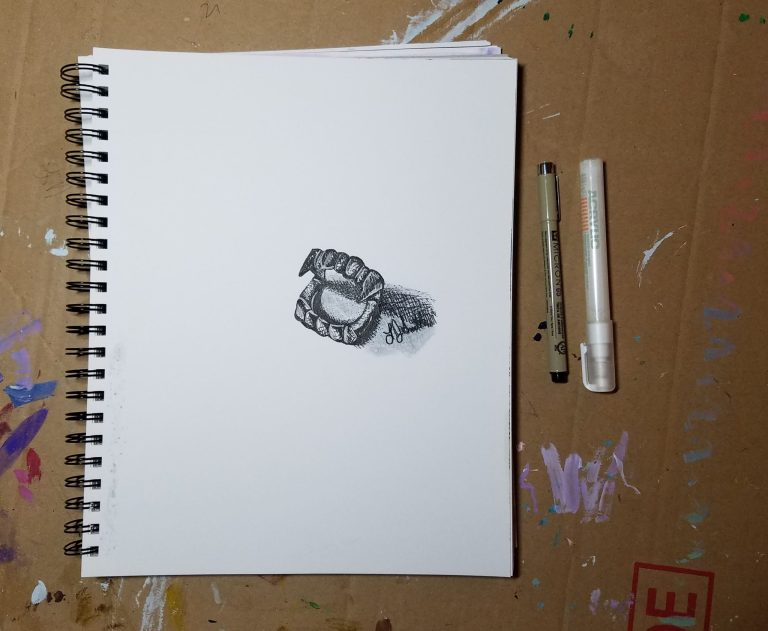 Sketchbook view with pens of Vampire Teeth by Laura Jaen Smith. Black and white ink drawing of toy vampire teeth.