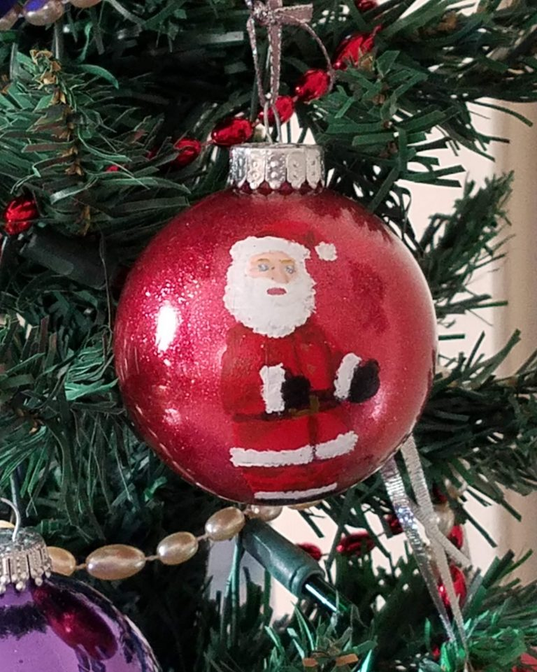 Red glitter ornament with hand-painted santa