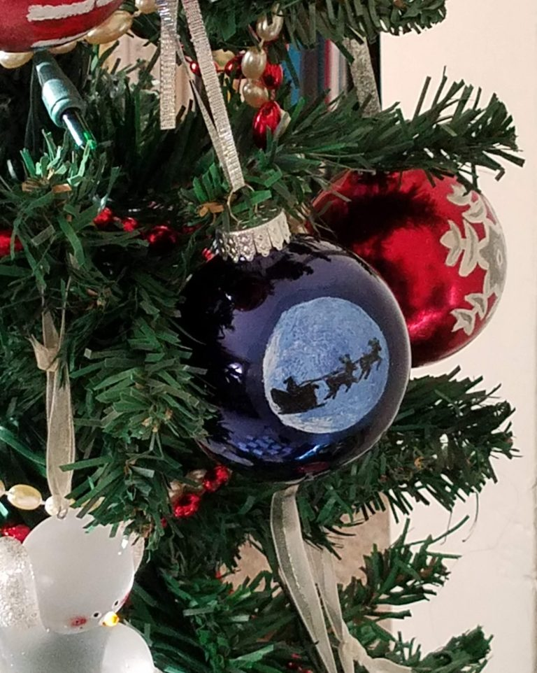Blue ornament with hand-painted santa's sleigh silhouette against moon