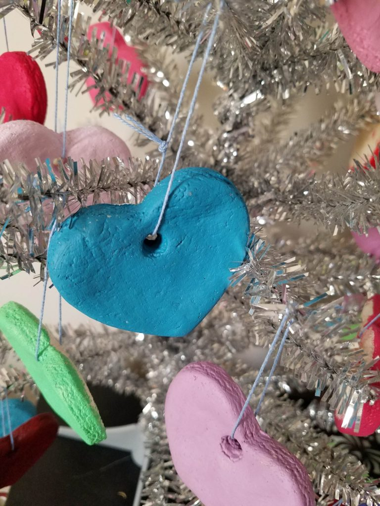 close up of blue DIY heart ornament on silver tree