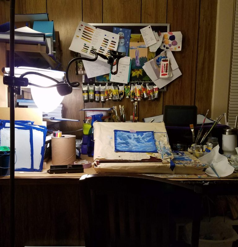 Picture of artist Laura Jaen Smith work space with cloud painting on tabletop easel