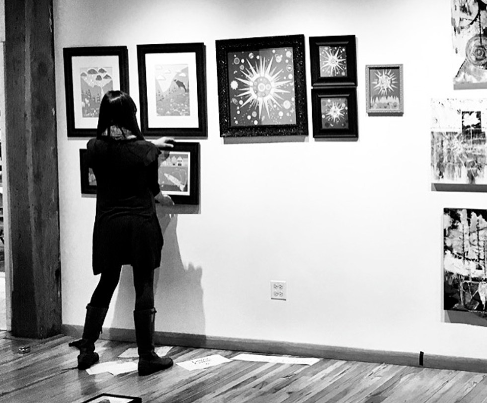 Laura Lynne Art hanging art in Water Street Studio Gallery