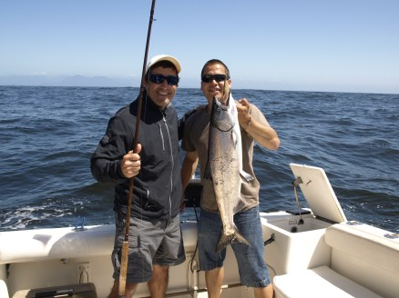 Catching a massive salmon with our guide.