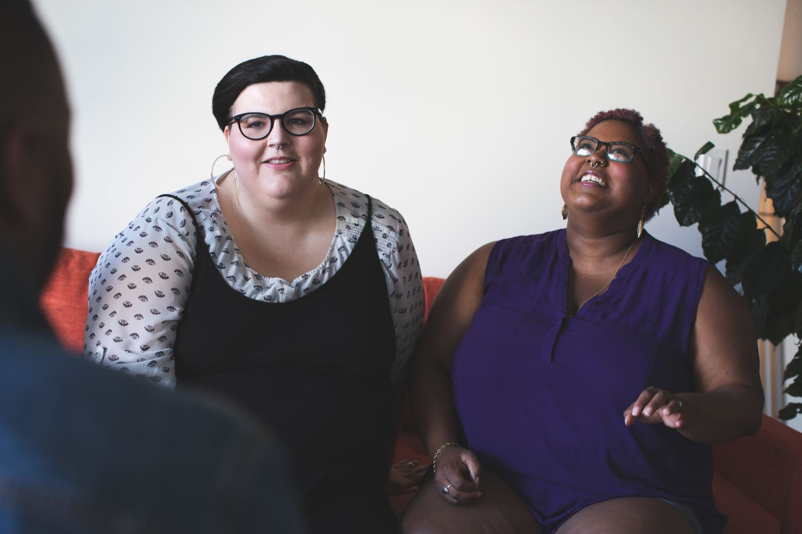 A couple is shown in a therapy office, sitting on a couch together. The white, plus size, androgynous member of the couple is wearing glasses and seems to be talking while their partner, a brown, plus size person wearing glasses throws back their head in laughter.