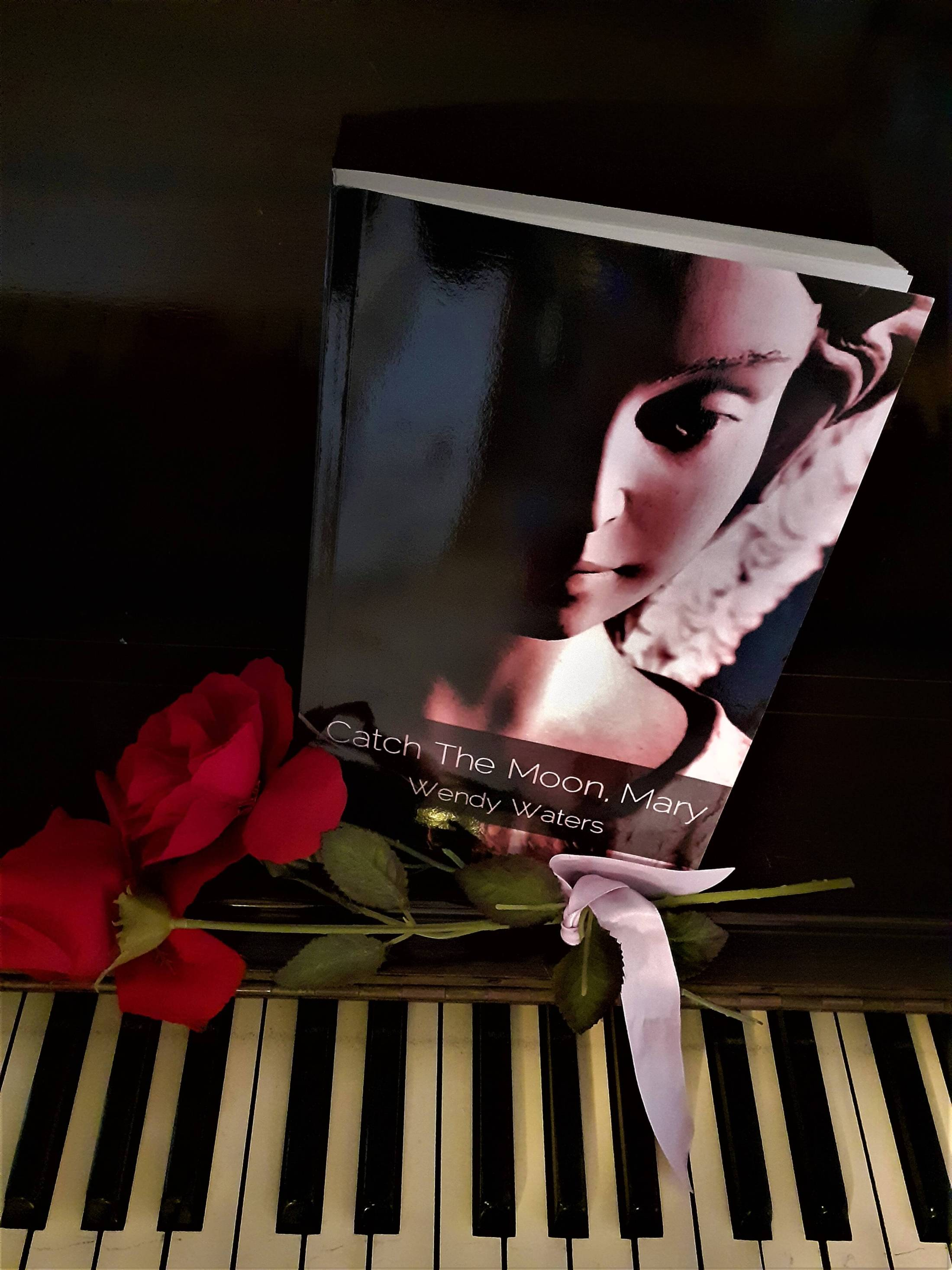 Catch the Moon Mary on a piano with roses
