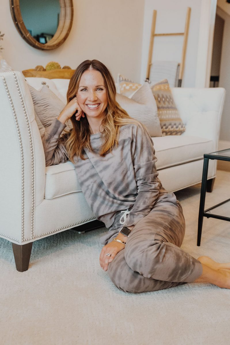 Laura in tie dye sweat suit, leaning against cream couch smiling at camera