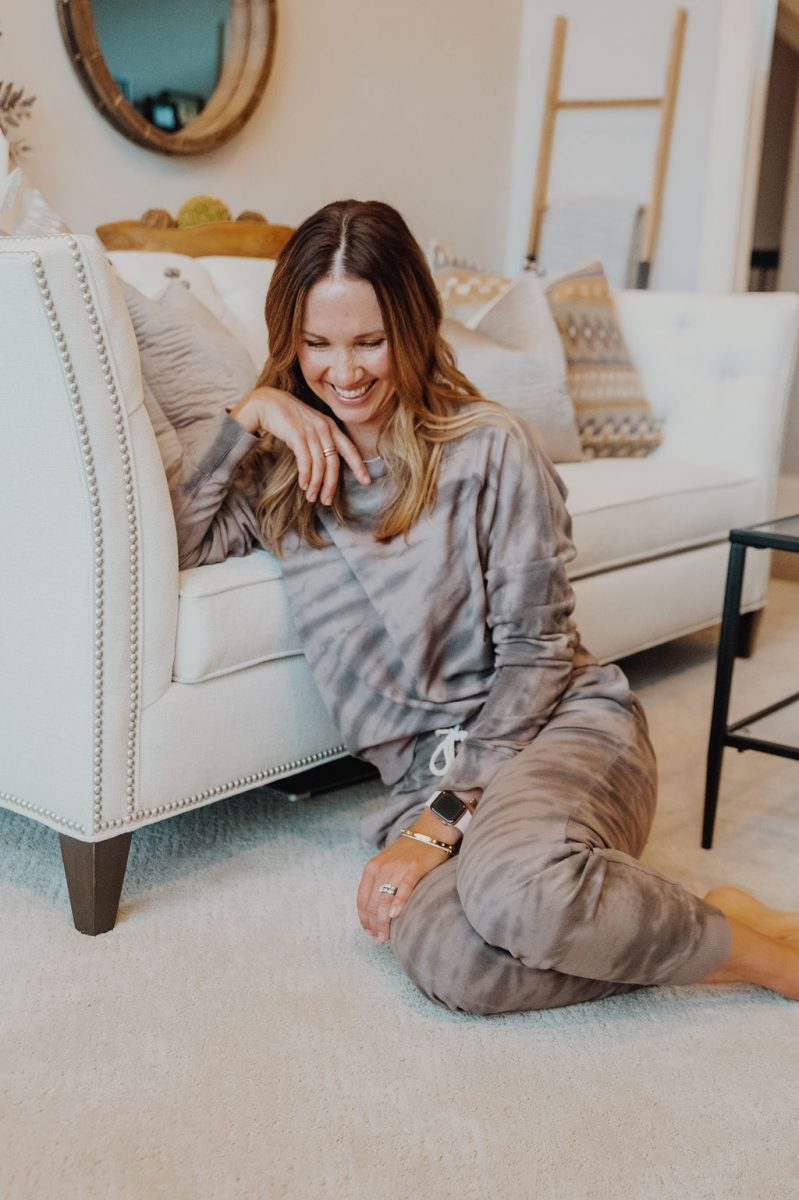Laura in tie dye sweatsuit, leaning against couch looking at floor