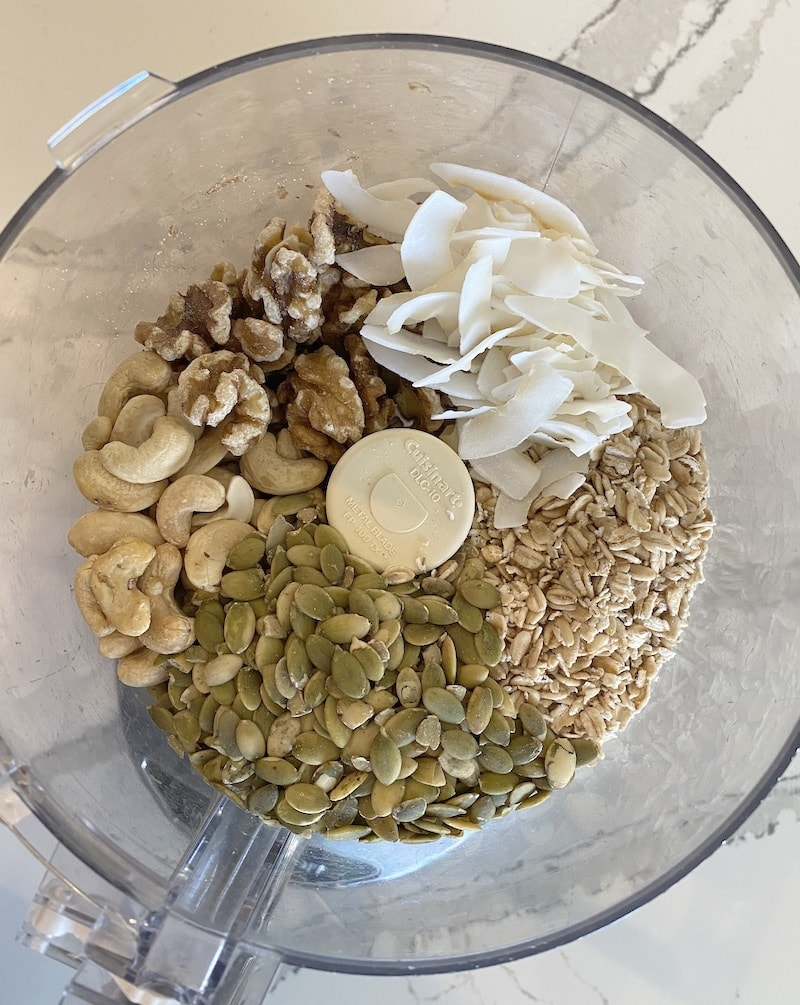 top view of food processor with oats, nuts and coconut read to be processed