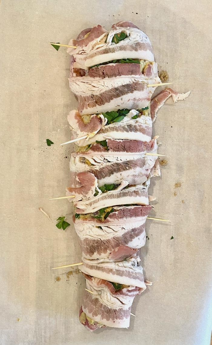 raw bacon wrapped around pork tenderloin secured with toothpicks