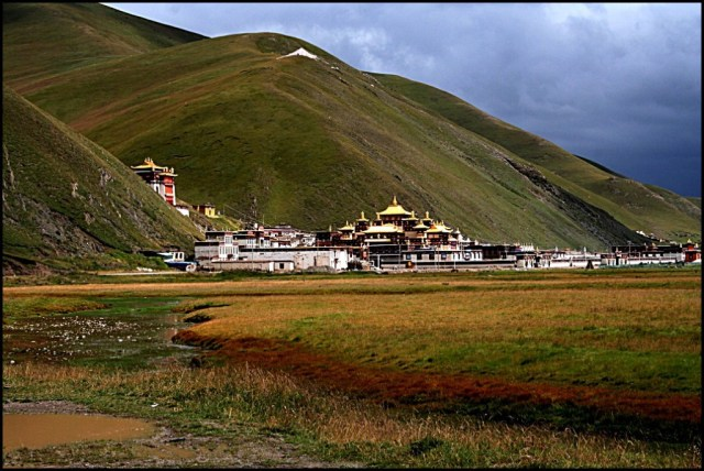 Classic scene in the Tibetan Plateau: outstanding landscape dotted with decrepit village and splendid temples